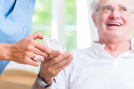prescription drugs: Nurse giving senior man prescription drugs