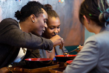 pareja comiendo: Amigos, los negros y latinos, comer sopa de fideos de ramen en japon�s restaurante Foto de archivo