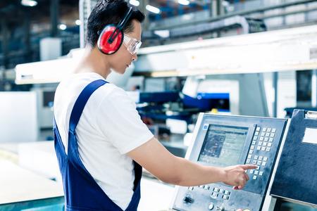 Trabajador introducción de datos en la máquina CNC en planta de la fábrica para obtener la producción va Foto de archivo - 47846959