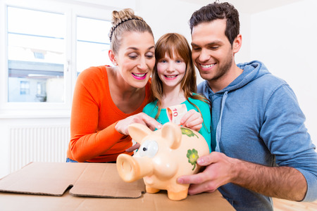 money and saving: Family saving money by moving house putting bank note in piggybank Stock Photo