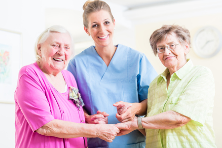 nursing care: Elderly care nurse with two senior women Stock Photo