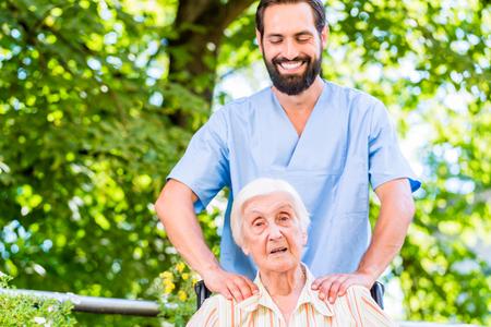 massage homme: Infirmière en gériatrie donnant massage senior femme Banque d'images