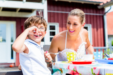 eating fruit: Mother with son eating fruit cake in front of house
