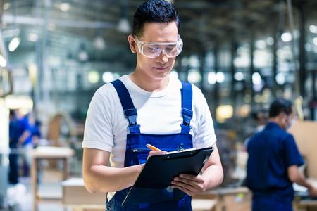 Operaio in impianto di produzione asiatico o in fabbrica a lavorare su lista di controllo con appunti