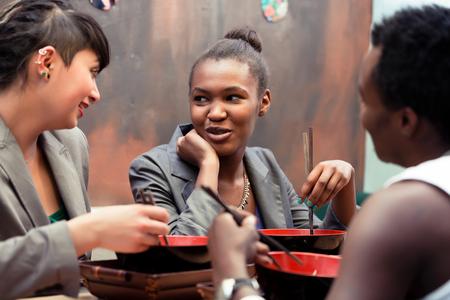 personas comiendo: Amigos, los negros y latinos, comer sopa de fideos de ramen en japonés restaurante Foto de archivo