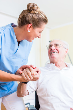 old carer: Nurse holding hand of senior man in rest home