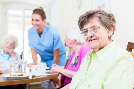 enfermeria: Grupo de personas mayores que tienen los alimentos en el hogar de ancianos, una enfermera está cumpliendo