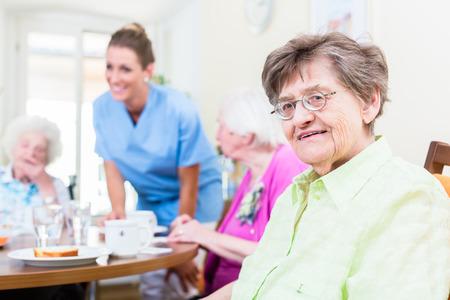 Gruppo di anziani che hanno il cibo in casa di cura, un infermiere sta scontando
