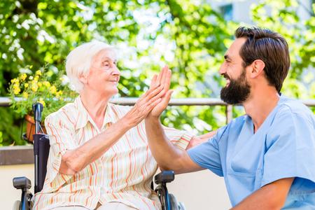seniors: Superior de la mujer y de la enfermera dando de alta cinco en casa guarder�a Foto de archivo