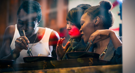 black couple: Man and women, black and Latin people, eating late in Korean eatery Stock Photo