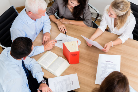 Lawyers in law firm reading documents and agreements at large conference table Foto de archivo