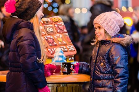 Kinder auf Weihnachtsmarkt mit Lebkuchen Lizenzfreie Bilder
