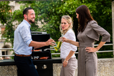co workers: Office colleagues grilling sausages at bbq after work on terrace