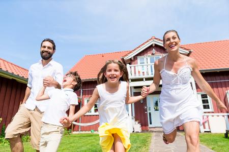Glückliche Familie auf Wiese vor dem Haus auf der Vorderseite Hof Gras Standard-Bild - 47847194