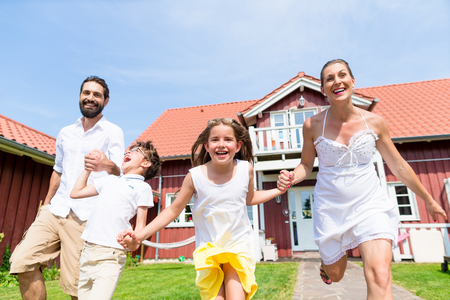 suburbs: Happy family running on meadow in front of house on front yard grass Stock Photo