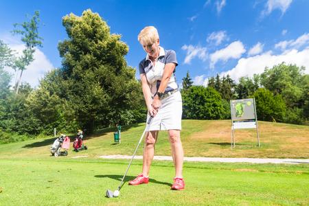 seniors: Senior woman doing tee stroke on golf course