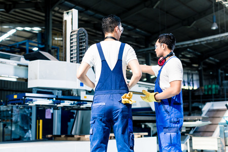 Worker team in factory discussing in front of machine
