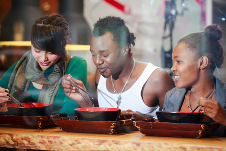 eatery: Man and women, black and Latin people, eating late in Korean eatery Stock Photo