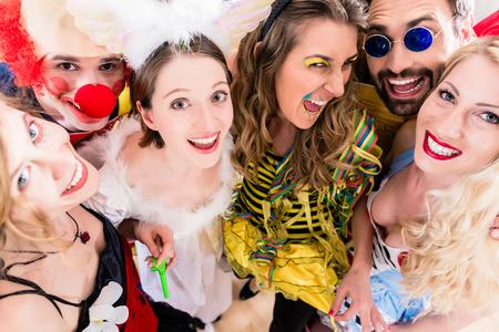 Les femmes et les hommes qui célèbrent à la fête pour la Saint-Sylvestre ou carnaval