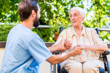geriatric nurse: Geriatric nurse holding hand of old woman in rest home