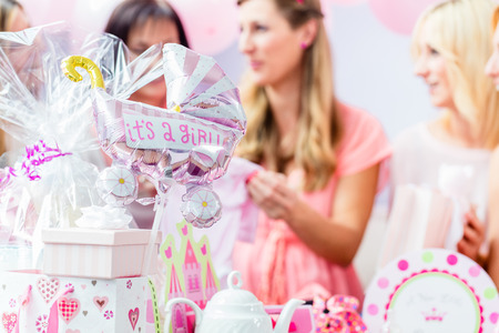 Best Friends on baby shower party celebrating giving kid stuff as present Foto de archivo