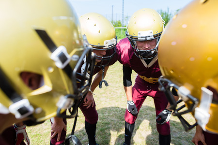 jugadores de futbol: Los jugadores de fútbol americano en apiñan estrategia Foto de archivo