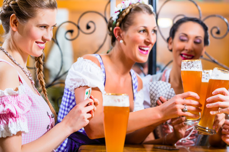 tracht: Friends playing cards in Inn or pub drinking beer