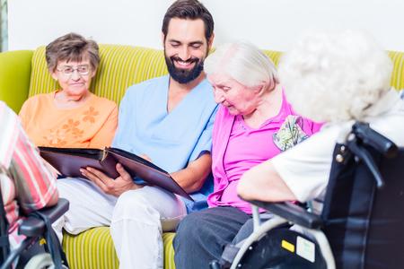 enfermera geriátrica mirando fotos con las personas mayores en el hogar guardería
