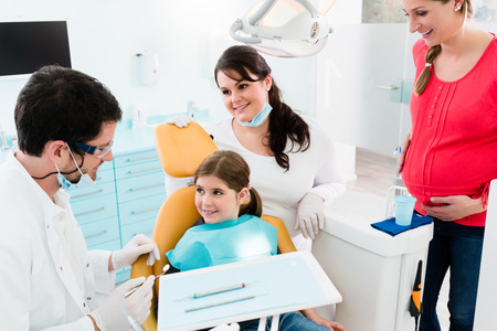 dental prophylaxis: Dentist giving dental treatment to child and mother