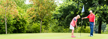 Senior woman and man playing golf putting on green