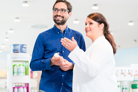 drug store: Man in drug store with sales lady shopping