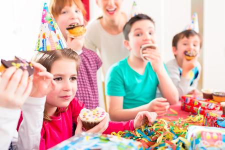 grabbing: Children grabbing muffins at birthday party and cake, the kids are wearing hats, balloons and paper streamers for decoration Stock Photo