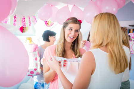 party friends: Woman giving gift to pregnant friend on baby shower party