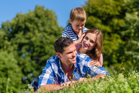 Familie liegen im Gras auf der jeweils anderen