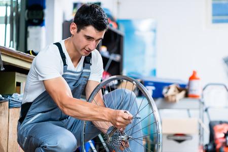 mecanico: El hombre como mecánico de bicicletas de trabajo en el taller