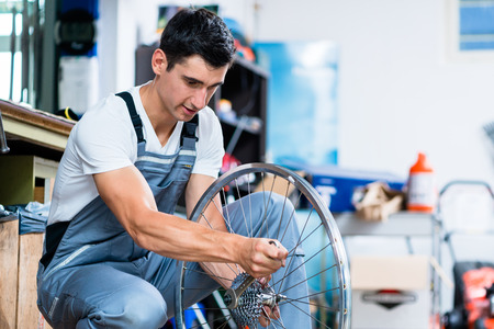 mechanics: Man as bicycle mechanic working in workshop