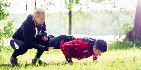 trainers: Sport couple outdoors with sling trainer