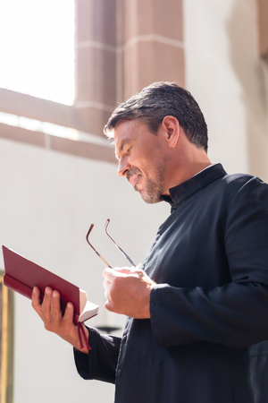 clergyman: Catholic priest reading bible in church