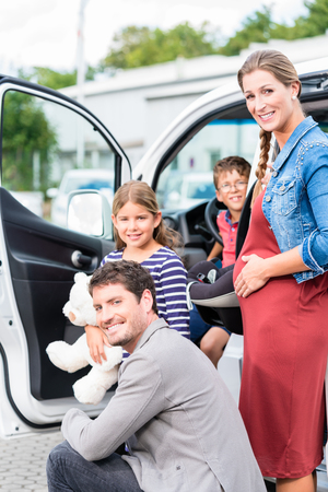 buying: Family buying car, mother, father and child at dealership with soft toy and special kid seat