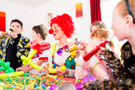 entertaining: Children celebrating birthday party with noisemakers while a clown is visiting entertaining the kids