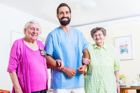 geriatric care: Caregiver with senior women in nursing home