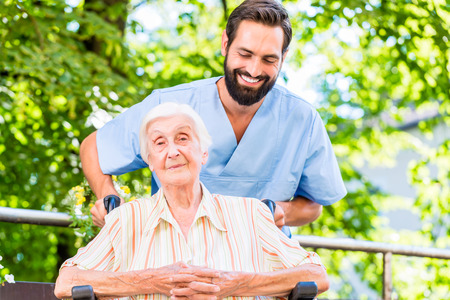 silla: Enfermera geriátrica que da masaje mujer mayor Foto de archivo