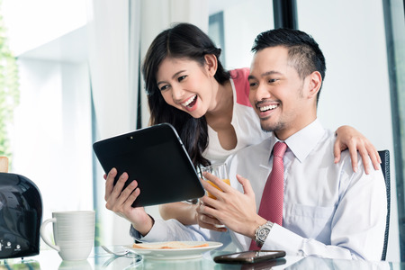 Aziatische paar met ontbijt voor de mens gaat naar kantoor, hij is het controleren van de e-mails of nieuws met zijn vrouw