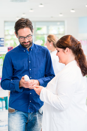 pharmacist: Pharmacist or drug store sales woman advising customer on care products for men