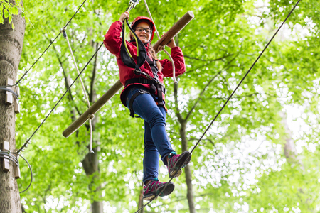 course: Child reaching platform climbing in high rope course