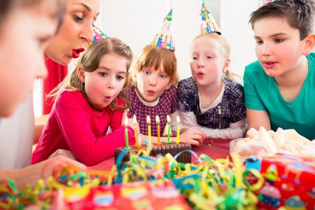 tortas de cumplea�os: Ni�o en la fiesta de cumplea�os soplando las velas en la torta siendo ayudado por amigos y la madre Foto de archivo
