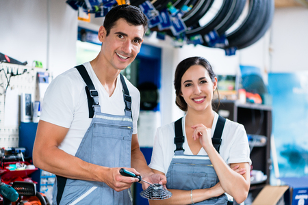 co workers: Woman and man as bike mechanics in workshop