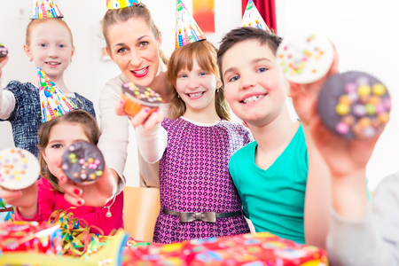 larger: Kids showing muffin cakes into the camera at birthday party, larger group of children and mother