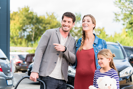 handsome young man: Mother, father, and child buying car at dealership, a new family auto