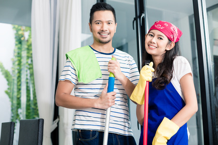 homemaker: Indonesian couple cleaning their home, wife and husband helping each other with the chore Stock Photo
